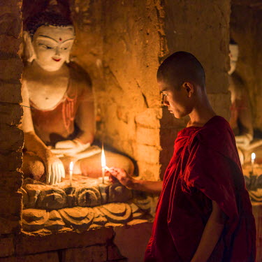 MYA2035AW Young novice monk in a buddhist temple light a candle on fire, Mandalay Region, Bagan, Myanmar, (MR)