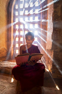 MYA2038AW Young burmese novice monk reading a book in a temple, Bagan, Mandalay region, Myanmar, (MR)