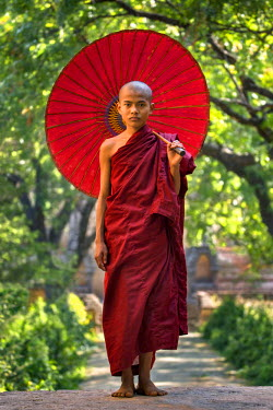 MYA2047AW Portrait of young novice monk under red umbrella, Mandalay Region, Bagan, Myanmar, (MR)