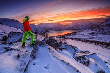 CLKRM53417 Hiker admires the frozen sea surrounded by snow framed by the orange sky at sunset Torsken Senja Troms County Norway Europe