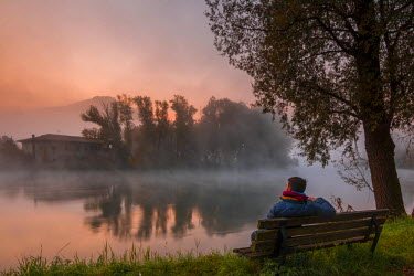 CLKAB52440 A man sitting on a bench watching a fisherman house and some trees reflected in Adda river with morning fog at dawn. Brivio, Lecco province, Lombardy, Italy, Europe
