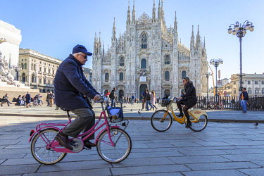 CLKRM51603 Cyclists under a warm spring sun in front of the facade of the Gothic Duomo Milan Lombardy Italy Europe