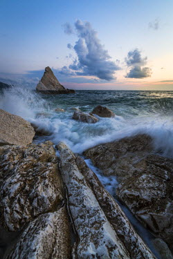 CLKRM51791 The lights of dusk on the waves crashing on cliffs La Vela Beach Portonovo province of Ancona Conero Riviera Marche Italy Europe