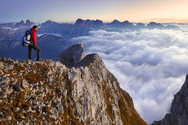 CLKMG52484 Europe, Italy, Veneto, Cadore, Auronzo. Hiker at dawn on the top of Cima dei Camosci, Marmarole, Dolomites, with sea of clouds in the valley