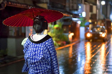 JAP0999AW Maiko with umbrella walking along a street, Gion district, Kyoto, Japan