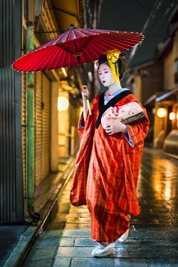 JAP1002AW Maiko wearing a traditional kimono and umbrella in the Gion district, Kyoto, Japan