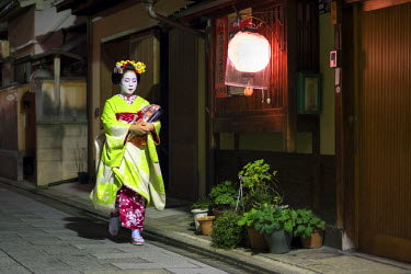 JAP1008AW Young Maiko in kimono walking along a street at night, Gion district, Kyoto, Japan