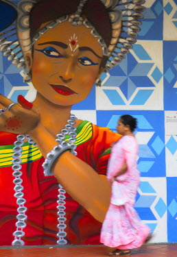 SNG1352AW Woman passing mural on wall, Little India, Singapore