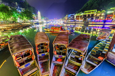 CH11234AW China, Hunan province, Fenghuang, traditional bamboo rafts and riverside houses reflecting in the river by night