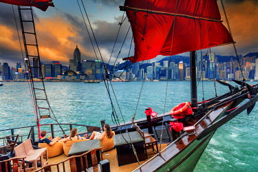 CH11292AW Hong Kong, tourist on a junk boat in Victoria harbor at sunset with Marina buildings in the background