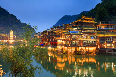 CH11355AW China, Hunan province, Fenghuang, riverside houses by night reflecting in the river