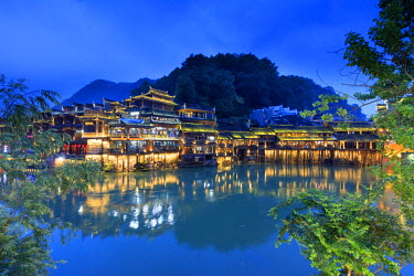 CH11356AW China, Hunan province, Fenghuang, riverside houses by night reflecting in the river