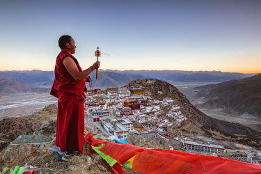 TIB0194AW Buddhist monk praying in front of Ganden monastery, Tibet, China (MODEL RELEASED)