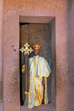 ETH3177 Ethiopia, Amhara Region, Lalibela.  An Ethiopian Orthodox priest with a processional cross at the door of Biete Amanuel rock-hewn church.
