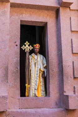 ETH3178 Ethiopia, Amhara Region, Lalibela.  An Ethiopian Orthodox priest with a processional cross at the door of Biete Amanuel rock-hewn church.