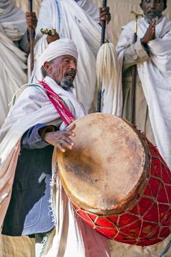 ETH3203 Ethiopia, Amhara Region, Lalibela.  A priest beats a religious drum at a service outside Biete Maryam church in Lalibela.