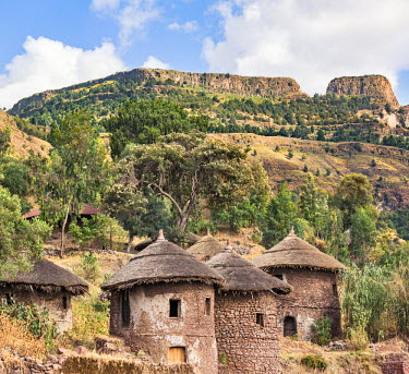 ETH3205 Ethiopia, Amhara Region, Lalibela.  Ethiopian double-storied round thatched-roofed houses, known as tukuls, with the mountain leading to Ashetan Maryam Monastery in the background.
