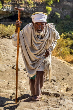 ETH3219 Ethiopia, Amhara Region, Lalibela, Neakutoleab.  An old priest climbs away from the ancient cave church of Neakutoleab, a short drive from Lalibela.