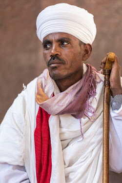 ETH3244 Ethiopia, Amhara Region, Lalibela. An Ethiopian Orthodox priest with prayer stick at the ancient rock-hewn church of Biete Amanuel.