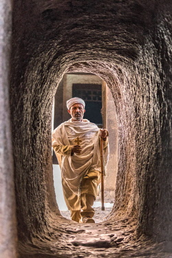 ETH3255 Ethiopia, Amhara Region, Lalibela. An Ethiopian Orthodox priest enters the rock passageway connecting Biete Medhane Alem to Biete Maryam rock-hewn churches.