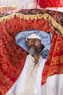 ETH3287 Ethiopia, Amhara Region, Lalibela. A priest carries a tabot (a replica of the Ark of the Covenant) on his head during the annual Timkat festival of the Ethiopian Orthodox Church which celebrates Epiph...