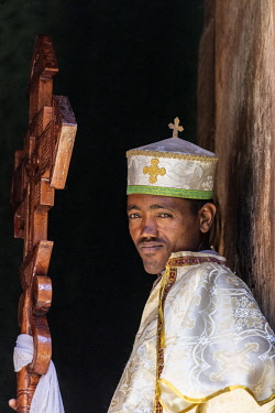 ETH3330 Ethiopia, Amhara Region, Lalibela. A deacon with a large wooden ceremonial cross stands at the entrance to the ancient rock-hewn church of Biete Giyorgis.