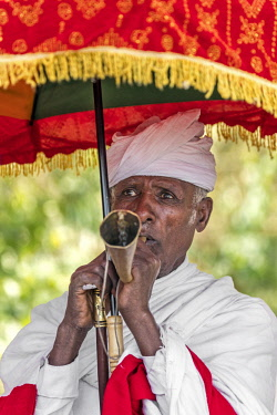 ETH3336 Ethiopia, Amhara Region, Lalibela. A priest blows a trumpet during the annual Timkat festival of the Ethiopian Orthodox Church which celebrates Epiphany.