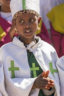 ETH3374 Ethiopia, Amhara Region, Lalibela. A schoolgirl from a church choir sings during the annual Timkat festival of the Ethiopian Orthodox Church which celebrates Epiphany.