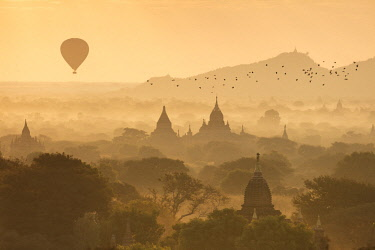 MYA2076AW Hot air balloons fly over the temples of Bagan at sunrise on a misty morning, Myanmar