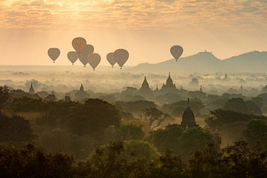 MYA2077AW Hot air balloons fly over the temples of Bagan at sunrise on a misty morning, Myanmar