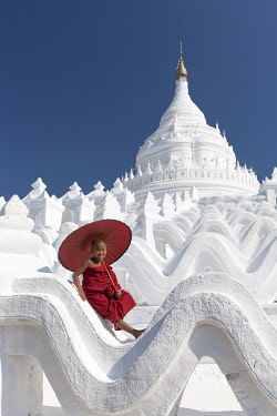 MYA2090AW Novice monk sits on the white wall of Hsinbyume Pagoda holding a red umbrella, Mingun, Mandalay
