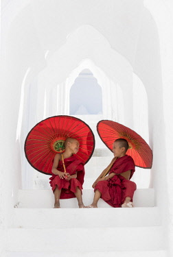 MYA2093AW Two young Buddhist monks holding red umbrellas have fun in Hsinbyume Pagoda, Mingun, Mandalay, Myanmar