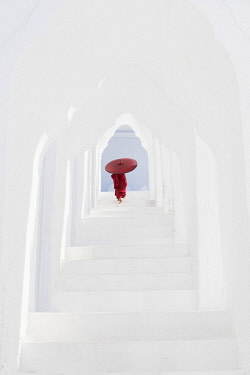 MYA2094AW A young Buddhist monk holding a red umbrella walks up the steps in Hsinbyume Pagoda, Mingun, Mandalay, Myanmar