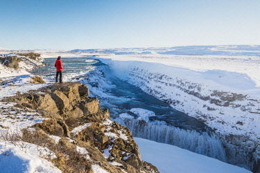 ICE4011AW Gullfoss waterfall, Golden Circle, Iceland. Man with red coat admiring the waterfall (MR)