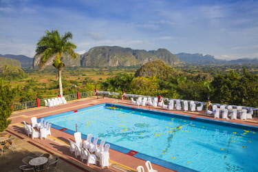 CB02662 Cuba, Pinar del Río Province, Vinales, View over Hotel Horizontes Los Jazmines swimming pool to Vinales valley - set up for a wedding party