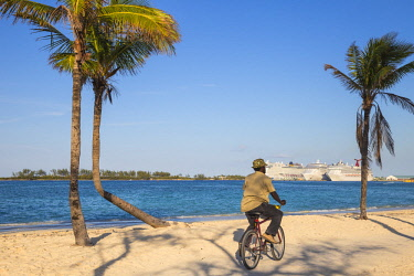 BA01408 Caribbean, Bahamas, Providence Island, Nassau, Man cycling past palm trees on white sand beach, with cruise ship in distance
