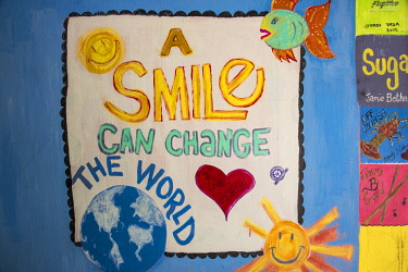 BA01277 Bahamas, Abaco Islands, Great Guana Cay, Nippers Bar, A smile can paint the world -painted on hut