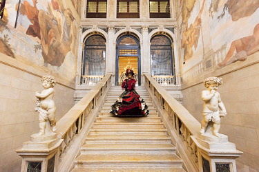 ITA10174AW Woman in costume standing on staircase in Ca Segredo palace during Carnival, Venice, Veneto, Italy