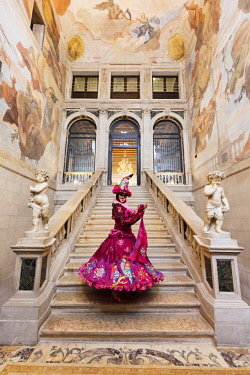 ITA10177AW Woman in costume standing on staircase in Ca Segredo palace during Carnival, Venice, Veneto, Italy