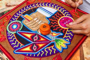 MEX1802AW Artist using colored thread to make traditional designs in Guanajuato, Mexico.