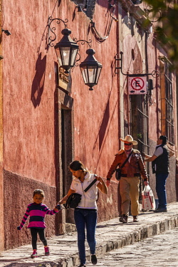MEX1842AW A mother and child walk along a sidewalk past old adobe buildings in the historic area of San Miguel de Allende, Mexico.