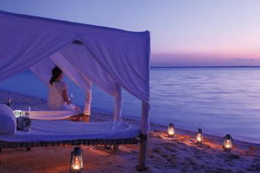 HMS2684937 Tanzania, Zanzibar, Kendwa, Kilindi Hotel, romantic lounge chairs on the shore at dusk