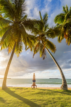 DMR0048AW Playa Moron, Las Terrenas, Samana Peninsula, Dominican Republic. Man practicing yoga on the beach at sunset (MR).