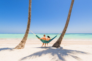 DMR0072AW Juanillo Beach (playa Juanillo), Punta Cana, Dominican Republic. Couple relaxing on a hammock on a palm-fringed beach (MR).