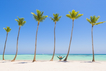 Juanillo Beach (playa Juanillo), Punta Cana, Dominican Republic. Couple relaxing on a hammock on a palm-fringed beach (MR). © AWL Images
