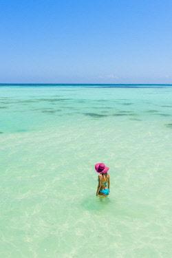 DMR0077AW Juanillo Beach (playa Juanillo), Punta Cana, Dominican Republic. Woman enjoying the clear waters in the Caribbean Sea (MR).