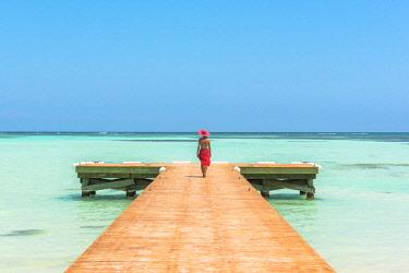 DMR0078AW Juanillo Beach (playa Juanillo), Punta Cana, Dominican Republic. Woman walkin on a wooden pier onto the Caribbean Sea (MR).