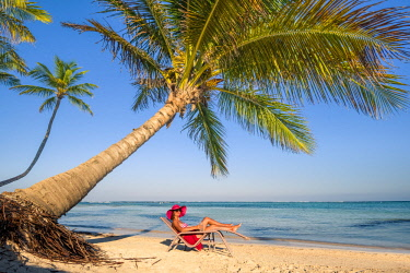 DMR0086AW Playa Blanca, Punta Cana, Dominican Republic, Caribbean Sea. Woman relaxing on the palm-fringed beach (MR).