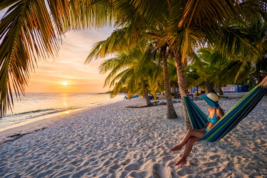 Mano Juan, Saona Island, East National Park (Parque Nacional del Este), Dominican Republic, Caribbean Sea. Beautiful woman on a hammock enjoying the sunset on the beach (MR). © AWL Images