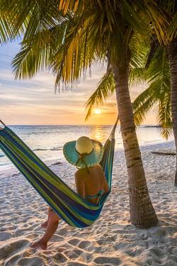 DMR0103AW Mano Juan, Saona Island, East National Park (Parque Nacional del Este), Dominican Republic, Caribbean Sea. Beautiful woman on a hammock enjoying the sunset on the beach (MR).
